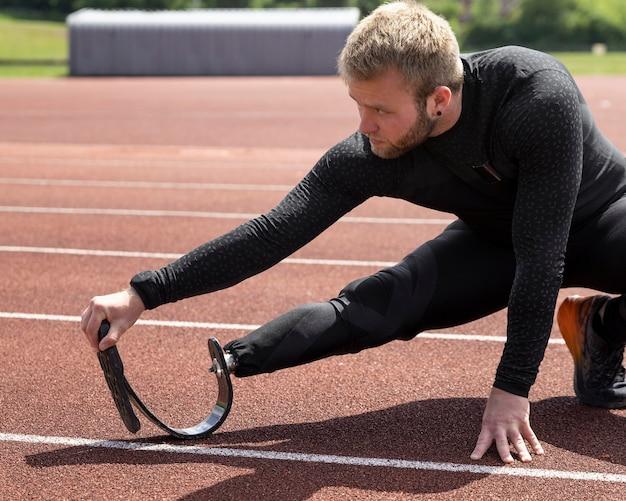 Homem com perna protética alongando tiro médio