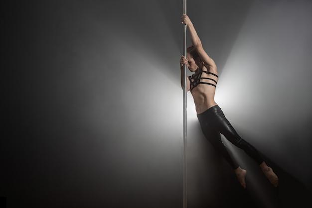 Homem com pilão, dançarina masculina dançando em um fundo preto