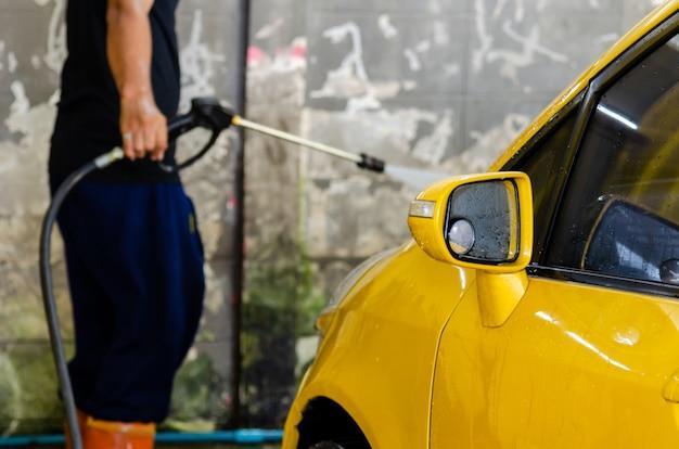 Homem com pistola de água de alta pressão para lavagem de carros