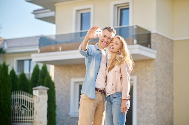 Homem com placa de casa abraçando a esposa