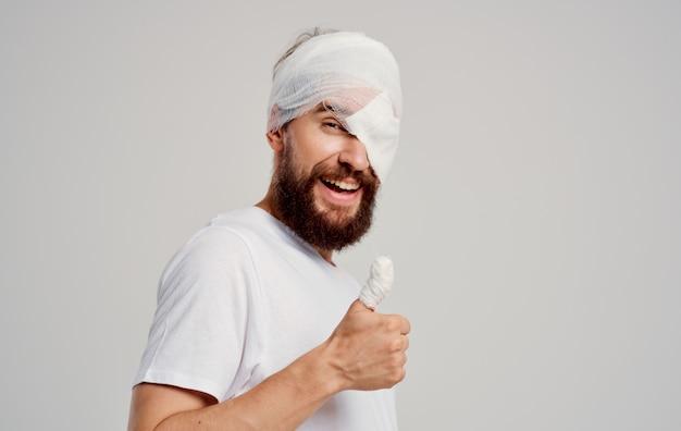Homem com polegar quebrado e cabeça enfaixada