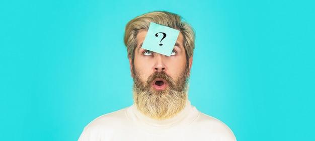 Homem com ponto de interrogação na testa, olhando para cima. notas de papel com pontos de interrogação. barba homem ponto de interrogação na cabeça, solução de problemas.
