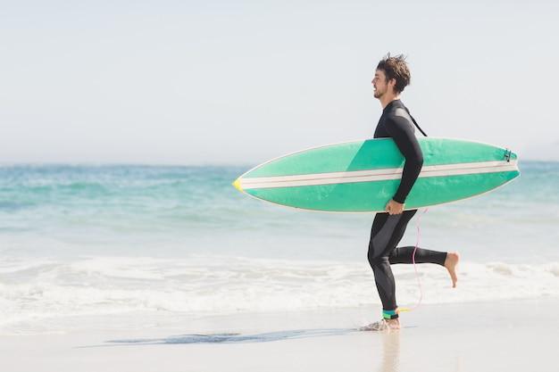 Homem com prancha correndo em direção do mar