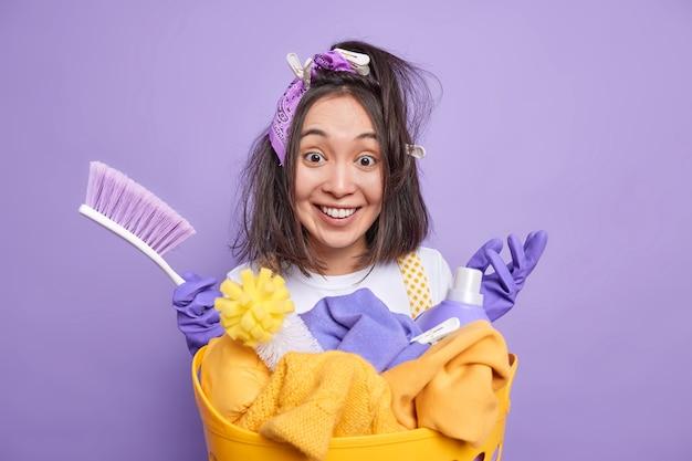 Homem com prendedores de roupa no cabelo segura escova ocupada limpando a casa sorri positivamente fica perto do cesto de roupa suja usa detergentes isolados em roxo vivo