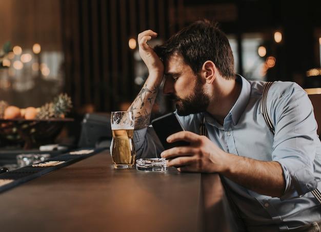 Homem com problemas, bebendo cerveja, fumando cigarro e usando telefone celular no pub