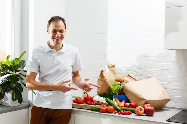 Homem com produtos frescos na mesa dentro de casa, closeup. serviço de entrega de comida