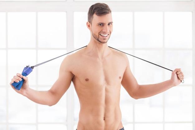 Homem com pular corda. jovem homem musculoso segurando uma corda de pular nos ombros e sorrindo para a câmera