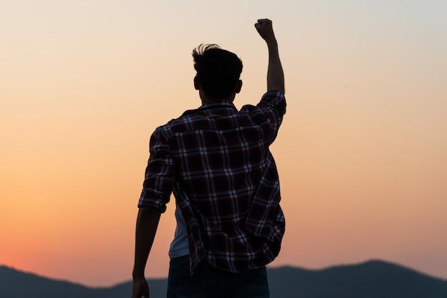 Homem com punho no ar durante o pôr do sol, sentindo-se motivado, liberdade