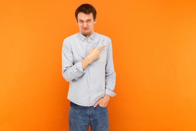 Homem com raiva apontando o dedo para o espaço da cópia e olhando para a câmera