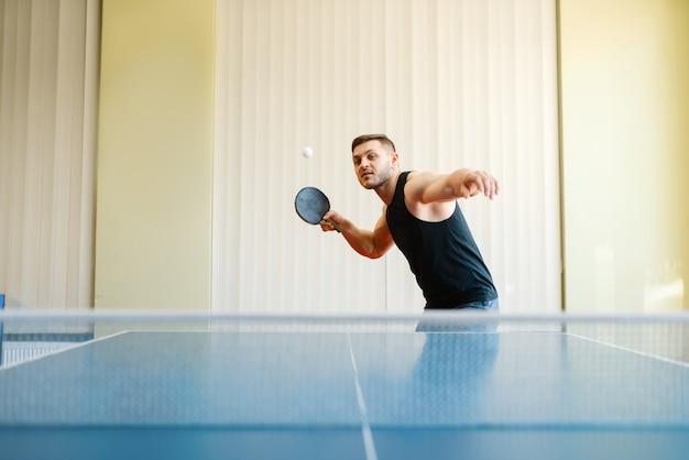 Homem com raquete e bola jogando pingue-pongue dentro de casa
