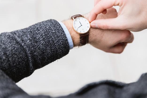 Homem com relógio verifica o tempo