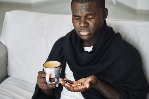 Homem com remédios nas mãos problema de descontentamento com dor de cabeça fria