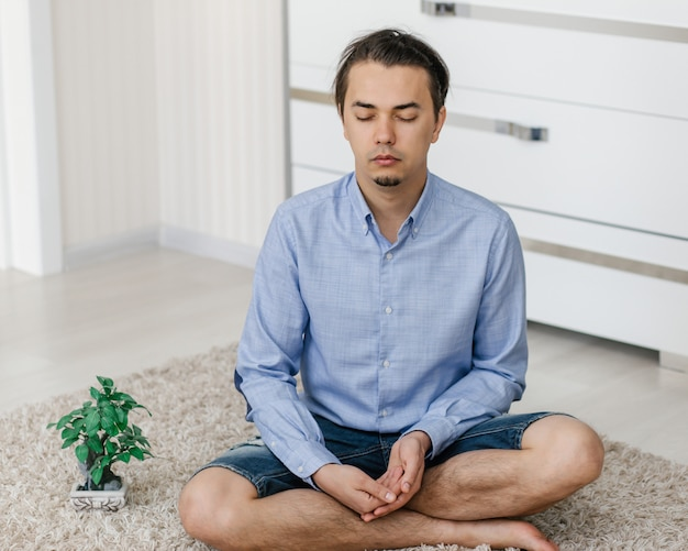 Homem com rosto calmo e olhos fechados faz meditação sentado no chão em casa