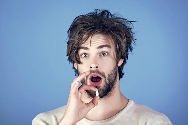 Homem com rosto surpreso segurando a pílula