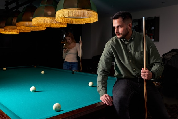 Homem com roupa casual se senta na mesa de bilhar, olhando para o jogo, o conceito de jogo de esporte de sinuca. retrato