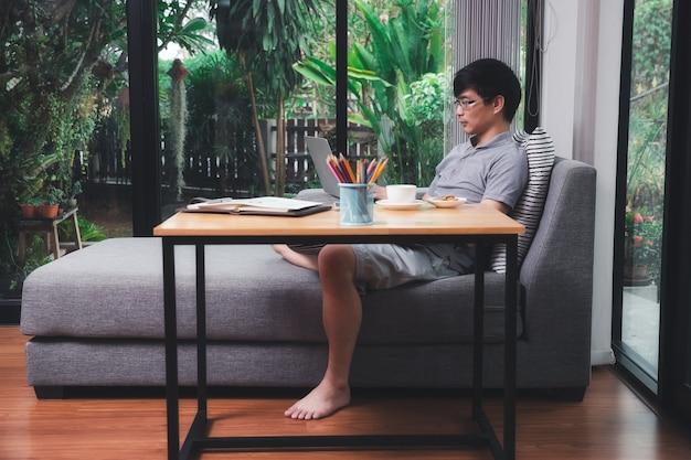 Homem com roupa casual, usando laptop, enquanto ele está trabalhando no escritório em casa.