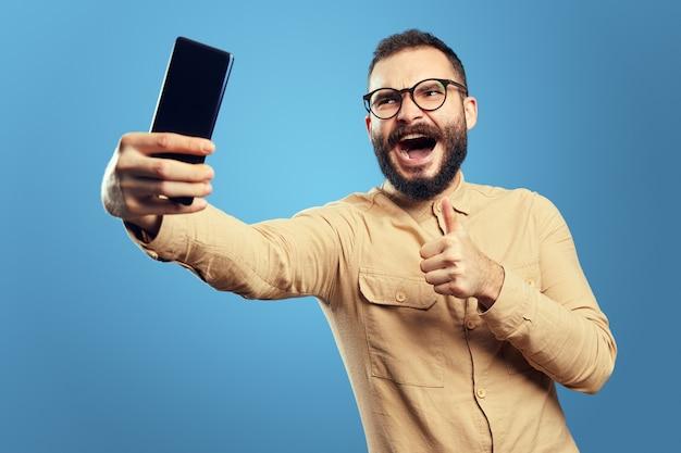 Homem com roupa da moda sorrindo e mostrando o polegar para cima gesto enquanto toma