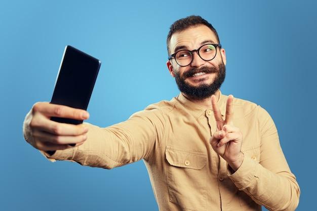 Homem com roupa da moda sorrindo e mostrando um gesto de paz enquanto tira uma selfie