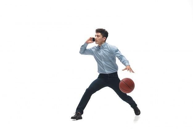 Homem com roupa de escritório jogando basquete no espaço em branco. incomum procure empresário em movimento, ação. esporte, estilo de vida saudável.