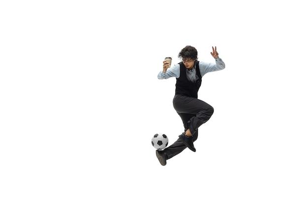 Homem com roupa de escritório, jogando futebol ou futebol com uma bola no fundo branco olhar incomum para