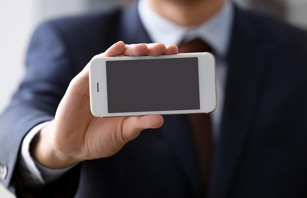 Homem com roupa de escritório segurando um smartphone com uma tela em branco