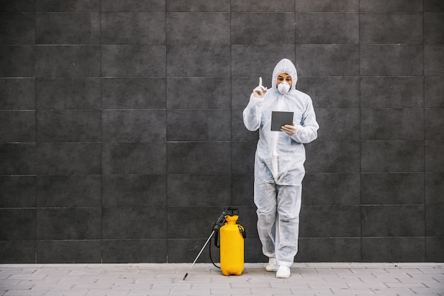 Homem com roupa de proteção contra vírus e máscara olhando e digitando no tablet, desinfetando edifícios de covid-19 com o pulverizador. prevenção de infecções e controle de epidemia. pandemia mundial.