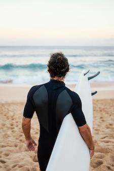 Homem com roupa de surfista caminhando na areia