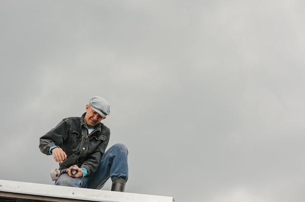 Homem com roupa de trabalho aperte os parafusos com uma chave de fenda no telhado contra um céu nublado.