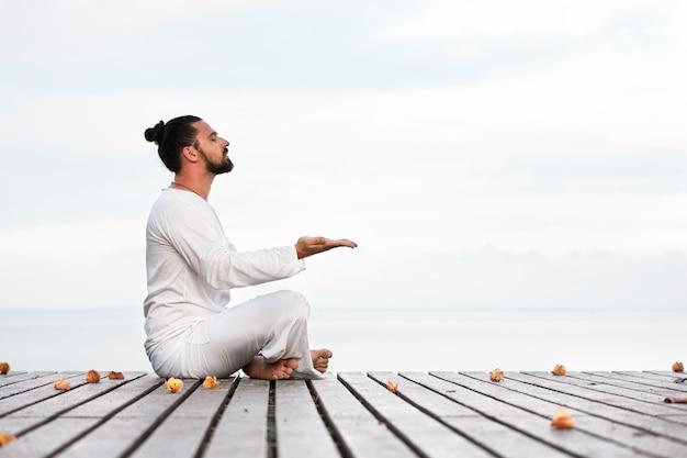 Homem com roupas brancas meditando ioga na plataforma de madeira