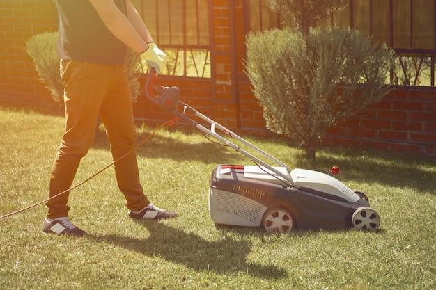Homem com roupas casuais e luvas está cortando a grama com um moderno cortador de grama em seu quintal, jardinagem ca ...