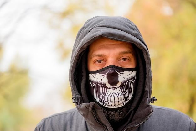 Homem com roupas de inverno na rua com uma máscara facial médica. closeup macho em um respirador para proteger contra a infecção pelo vírus da gripe ou coronavírus. homem com máscara protetora na rua