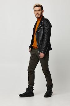 Homem com roupas de marca, jaqueta de couro laranja suéter calças modelo