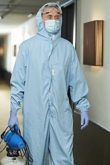Homem com roupas de proteção especial indo para desinfetar quartos de hotel
