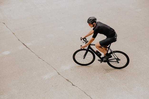 Homem com roupas esportivas, treinando em bicicleta ao ar livre
