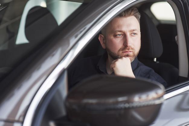 Homem com roupas oficiais experimentando seu novo carro em salão de automóveis