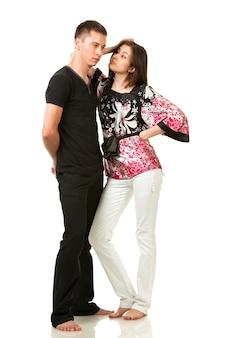 Homem com roupas pretas e mulher com blusa multicolorida posando em pose engraçada e olhando um para o outro