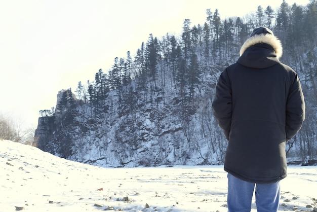 Homem com roupas quentes em pé na floresta e olhando montanhas nevadas