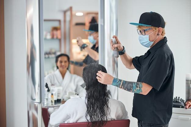Homem com roupas totalmente pretas cuidando do cabelo