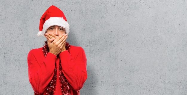 Homem com roupas vermelhas, celebrando as férias de natal, cobrindo a boca com as duas mãos