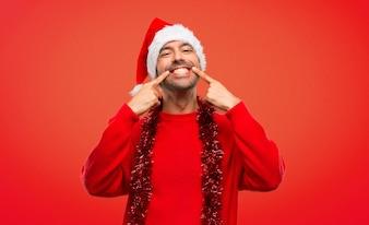 Homem com roupas vermelhas, celebrando as férias de Natal sorrindo enquanto apontava a boca