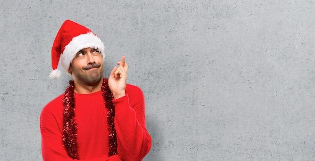 Homem com roupas vermelhas, comemorando as férias de natal com os dedos cruzando e desejando