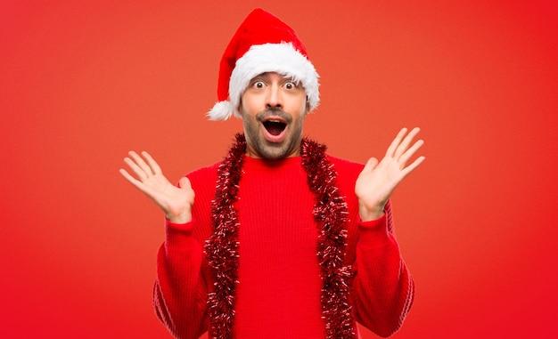 Homem com roupas vermelhas, comemorando as férias de natal com surpresa e chocado