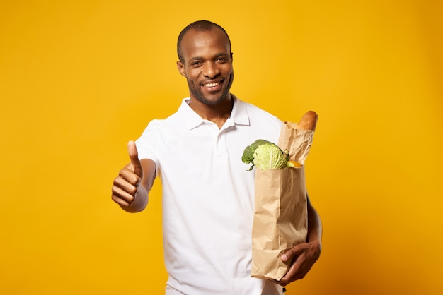 Homem com saco de papel de produtos frescos, aparecendo o polegar.
