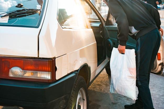 Homem com saco de plástico branco falando com o motorista pela porta aberta do passageiro.