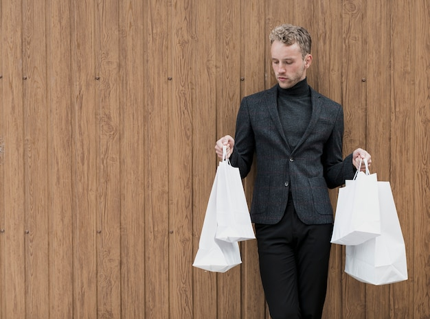 Homem com sacolas de compras em fundo de madeira