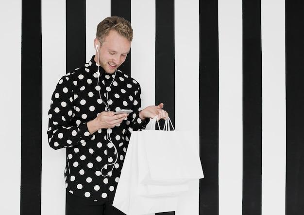 Homem com sacolas de compras em um fundo listrado