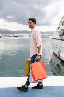 Homem com sacolas de compras perto do porto
