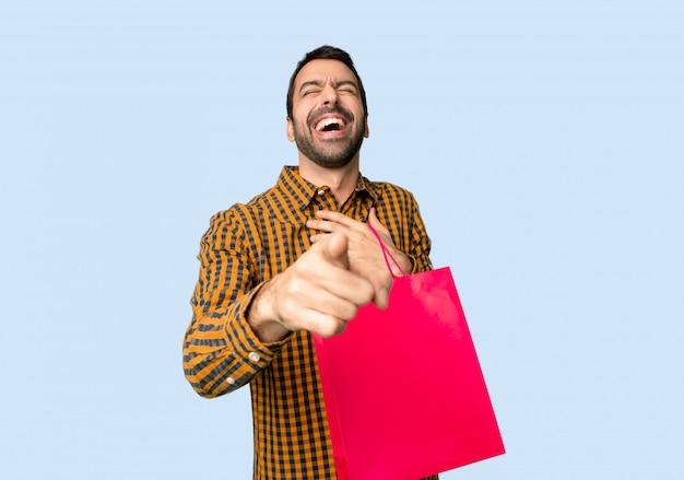 Homem com sacos de compras, apontando com o dedo para alguém e rindo muito