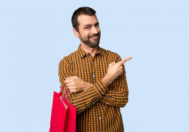 Homem com sacos de compras, apontando para o lado para apresentar um produto no fundo azul isolado