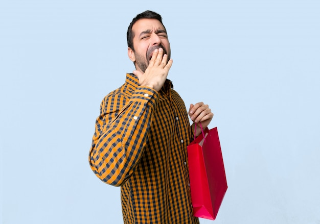 Homem com sacos de compras, bocejando e cobrindo a boca aberta com a mão no fundo azul isolado